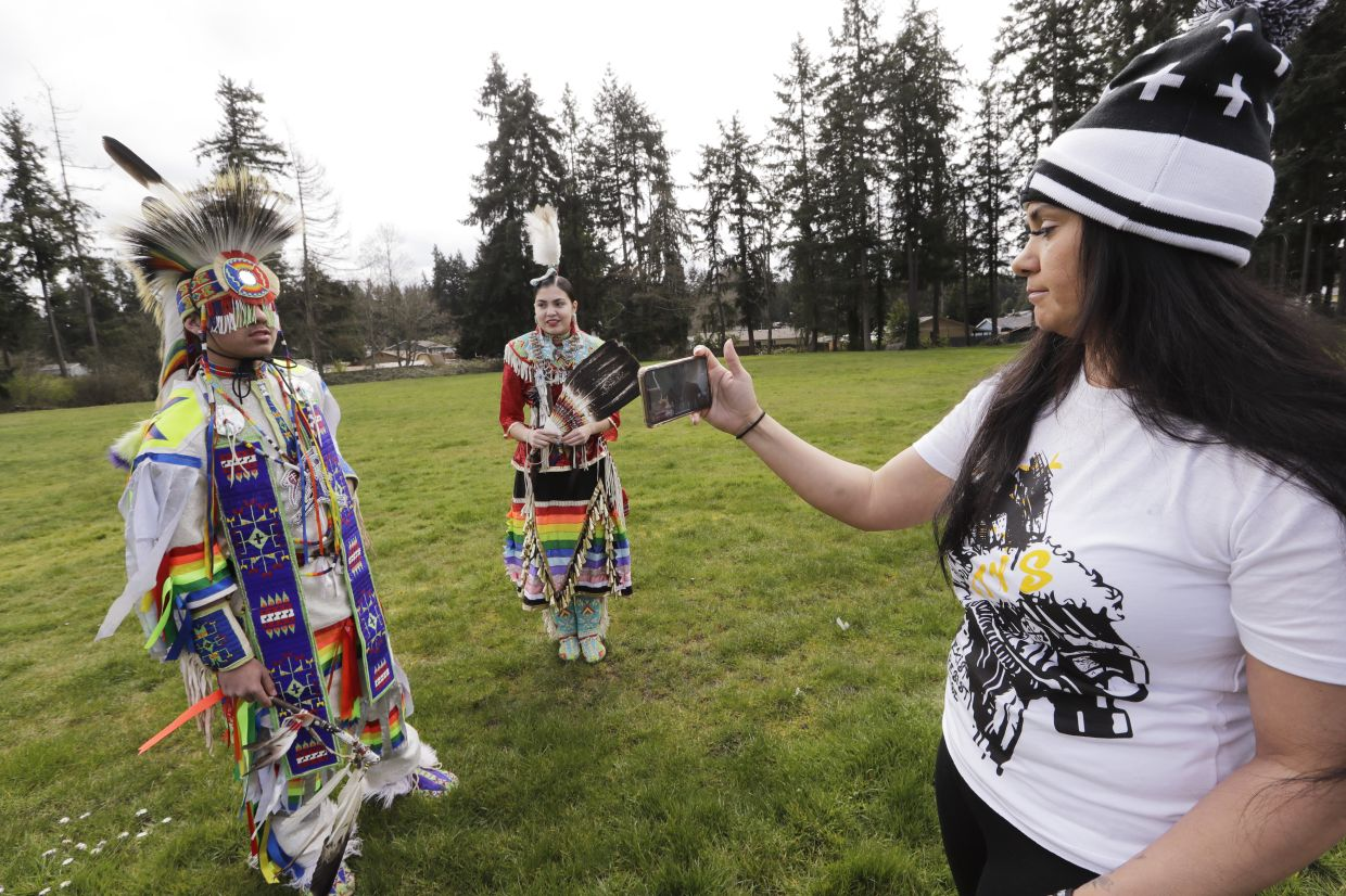 Wakiyan Cuny, 16, left, and his sister Wicahpi Cuny, 14, Dakota and Lakota tribal members, wear ceremonial clothing while they are filmed by their mother Tera Baker during a live streamed powwow from a park near their home in Puyallup, Washington.