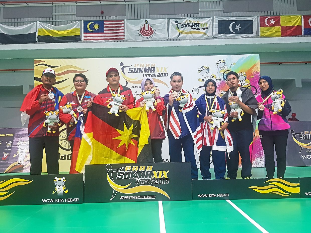 Tan (fifth from left) bagged the bronze medal in the Men's Single and Mixed Doubles categories at Para Sukma 2018.
