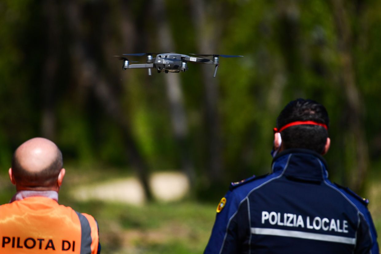 An officer of the municipal police (R), assisted by an instructor, pilots a DJI Mavic 2 Enterprise drone equipped with a thermal sensor for checking people's temperature on April 9, 2020 in Treviolo, near Bergamo, during the country's lockdown aimed at stopping the spread of the Covid-19 pandemic, caused by the novel coronavirus.