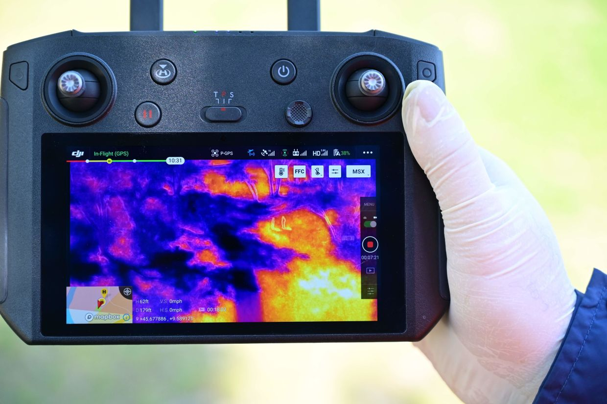 An officer of the municipal police shows the thermal imaging produced by a DJI Mavic 2 Enterprise drone equipped with a thermal sensor for checking people's temperature in Treviolo, near Bergamo, during the country's lockdown aimed at stopping the spread of the Covid-19 pandemic.