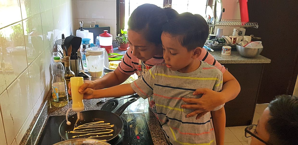 Suhana's children like watching her and helping her with simple tasks in the kitchen. — SUHANA ISHAK