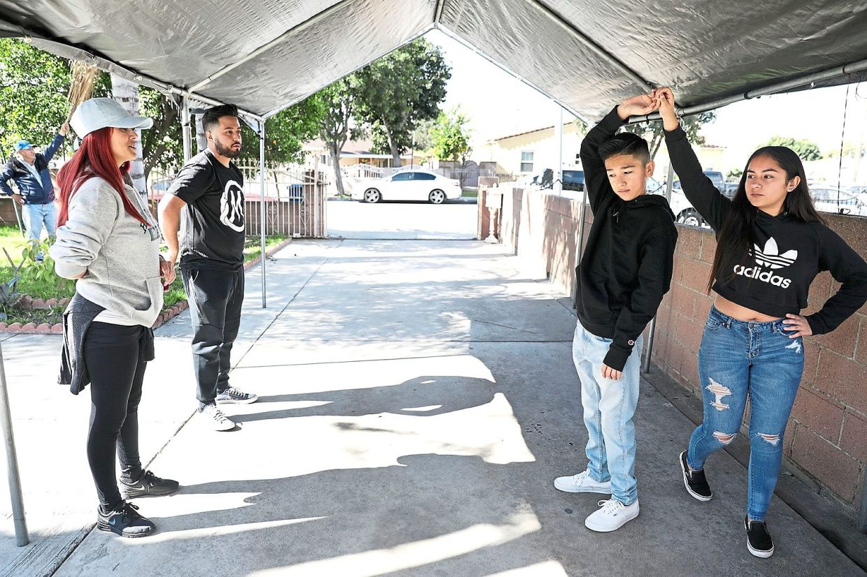 Cynthia Garcia (left) and her assistant Salvador Ruiz (second from left) conducting a dance practice with Marc Morales, 11, and Ashley Soltero, 14, for Ashley's upcoming quinceanera.