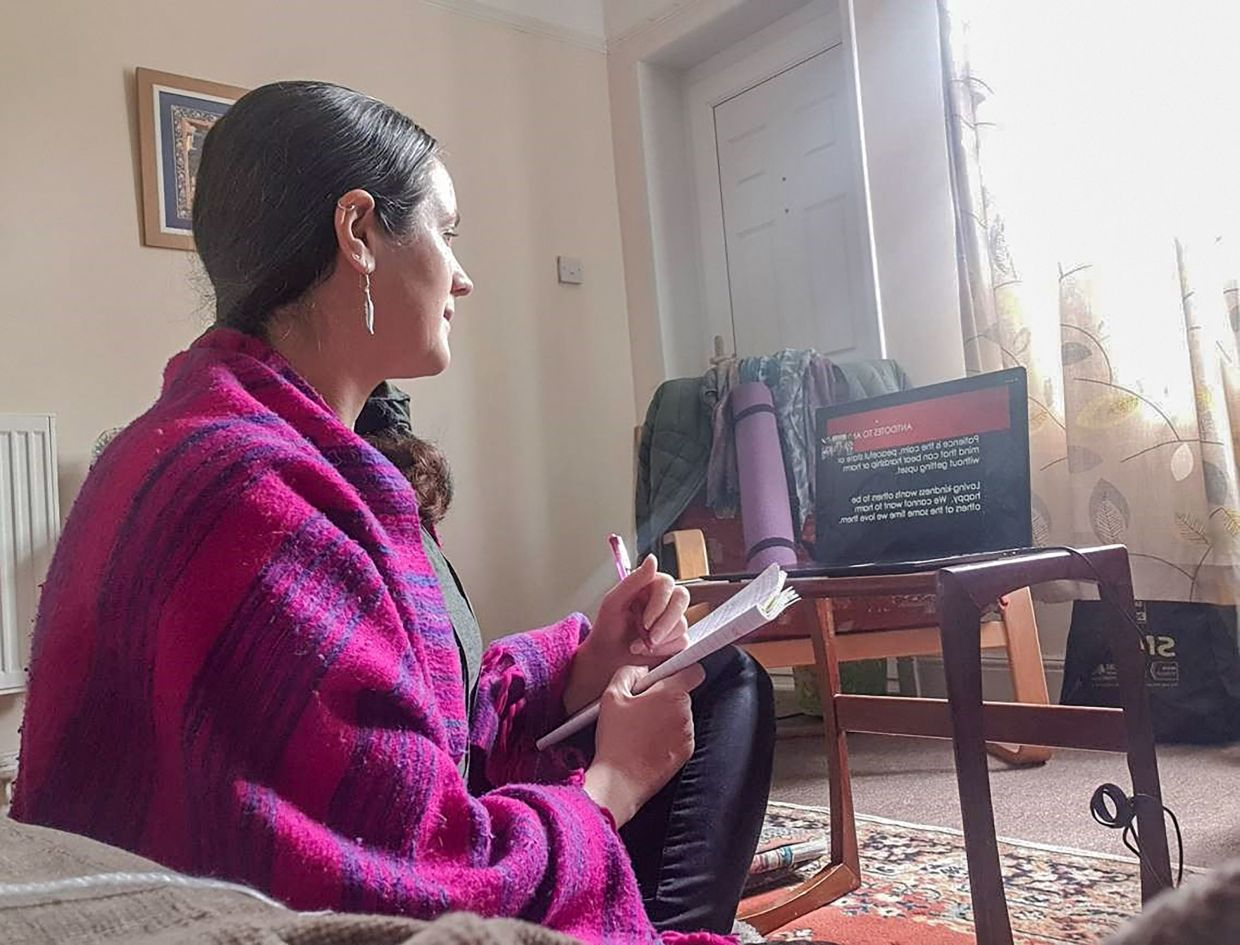 Roache takes part in an online Buddhism course from a living room in Norfolk, England. — AFP