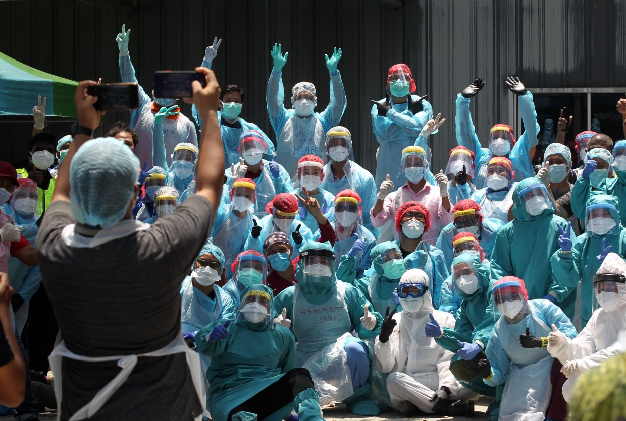 Health Ministry personnel taking a group photo after completing Covid-19 screening tests at Jalan Alang in Kampung Baru. KAMARUL ARIFFIN/The Star
