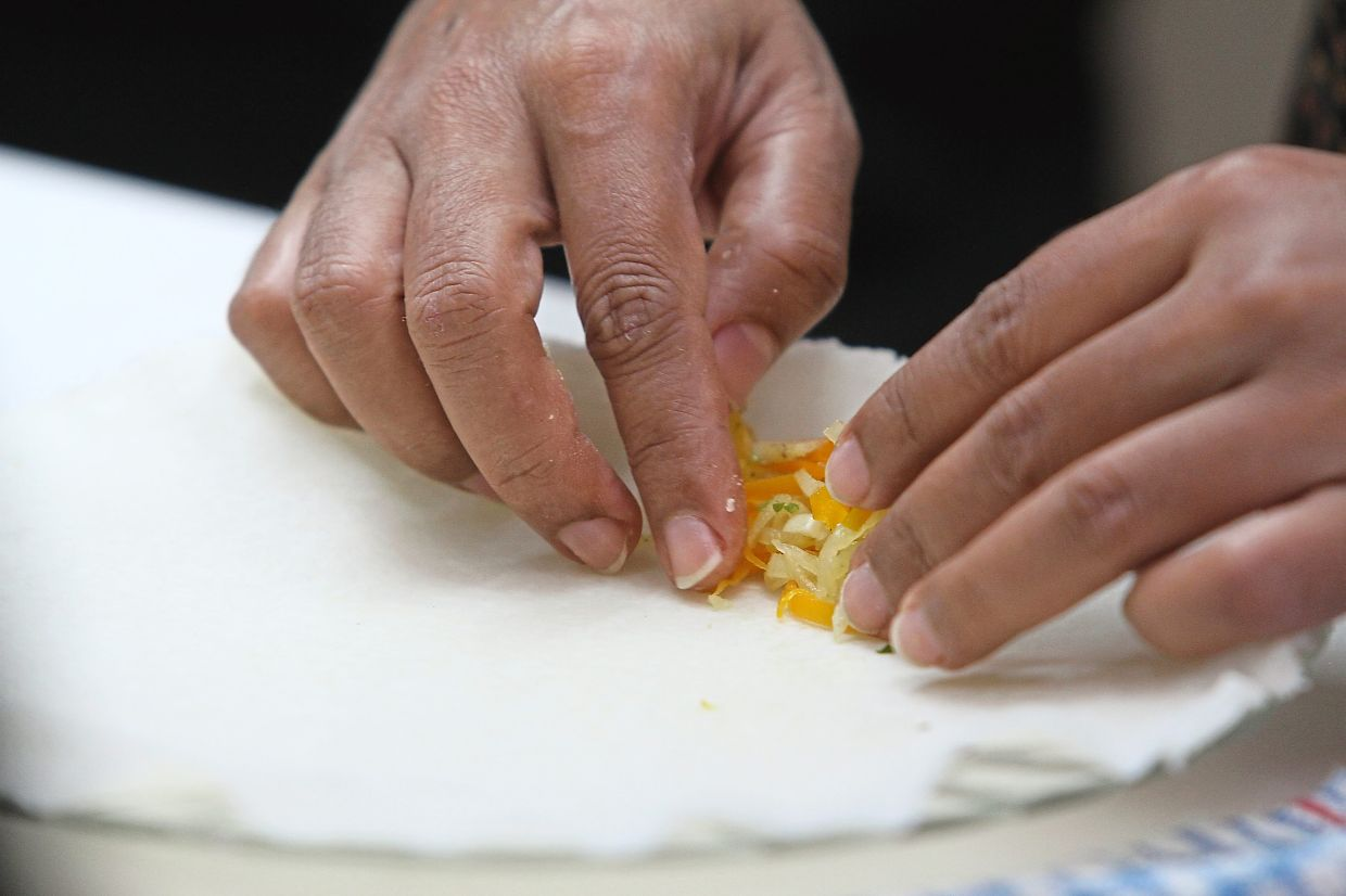 A tablespoon of filling is placed on the skin before rolling it up.