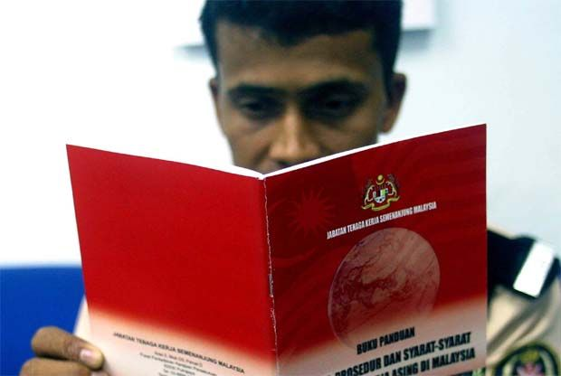 Nepali security guard Kul Bahadur, 24, reads the guide book by the Labour Department that containes policies, procedures and regulations governing the employment of foreign workers in Malaysia. - The Star filepic