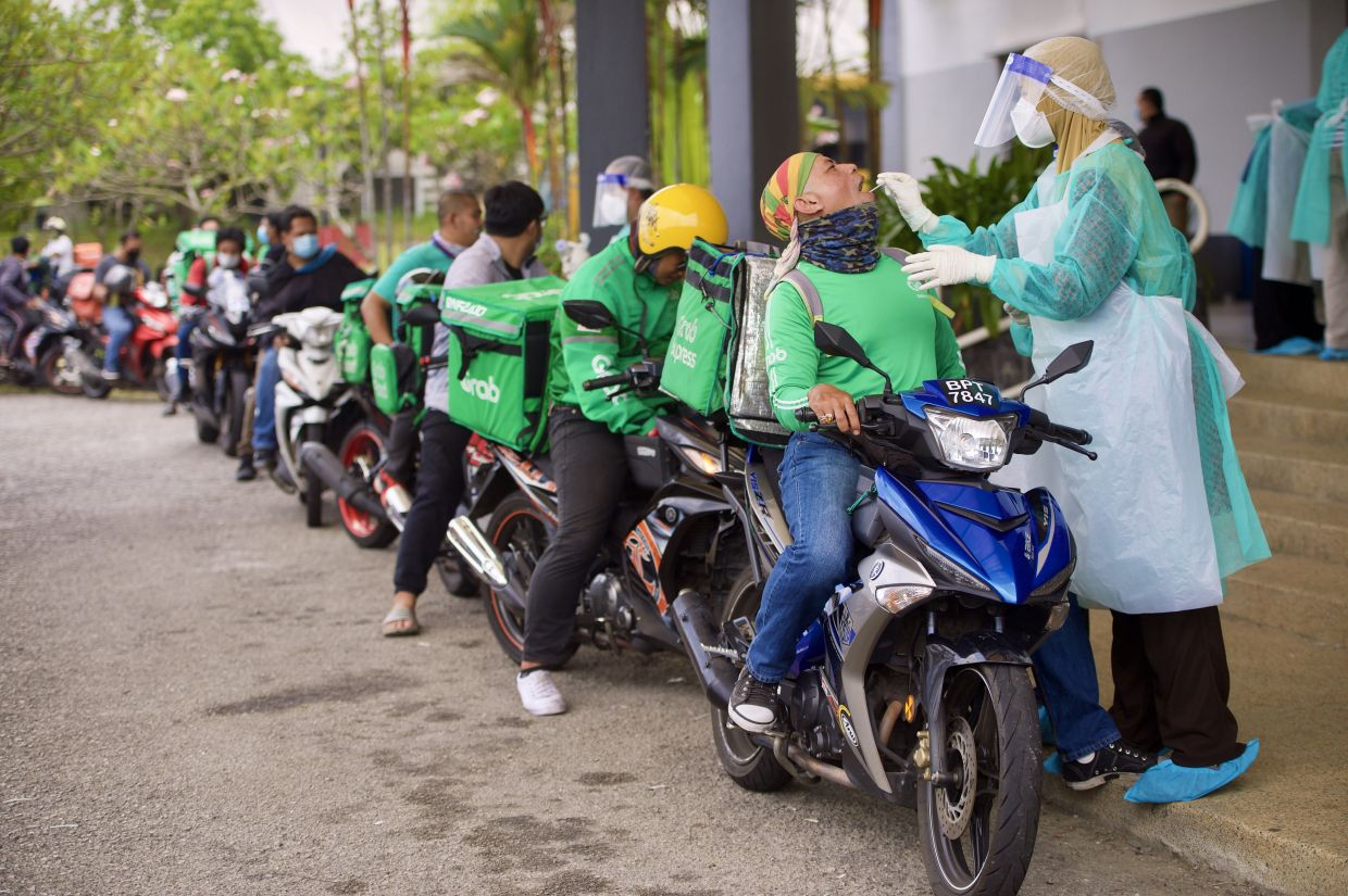Delivery riders queuing to get their free drive-thru Covid-19 screening at Dewan Raja Muda Musa in Section 7, Shah Alam. The screening is funded by the Selangor state government and being conducted by SelCare. RAJA FAISAL HISHAN/The Star