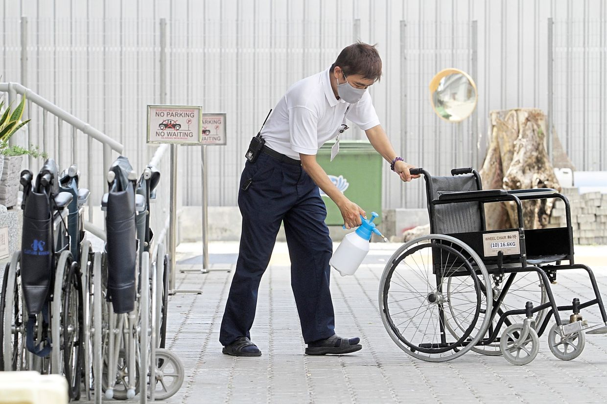 A Tzu Chi member spraying disinfectant to sanitise wheelchairs used by kidney patients receiving treatment at the Tzu-Chi dialysis centre.