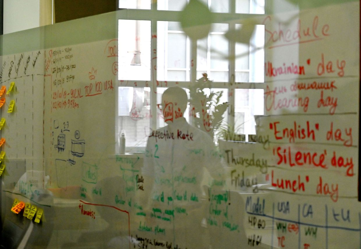 Voloshyn, the co-founder and chief technical officer of the Preply language learning platform, is reflected in a glass as he examines a blackboard at his empty office in Kiev.