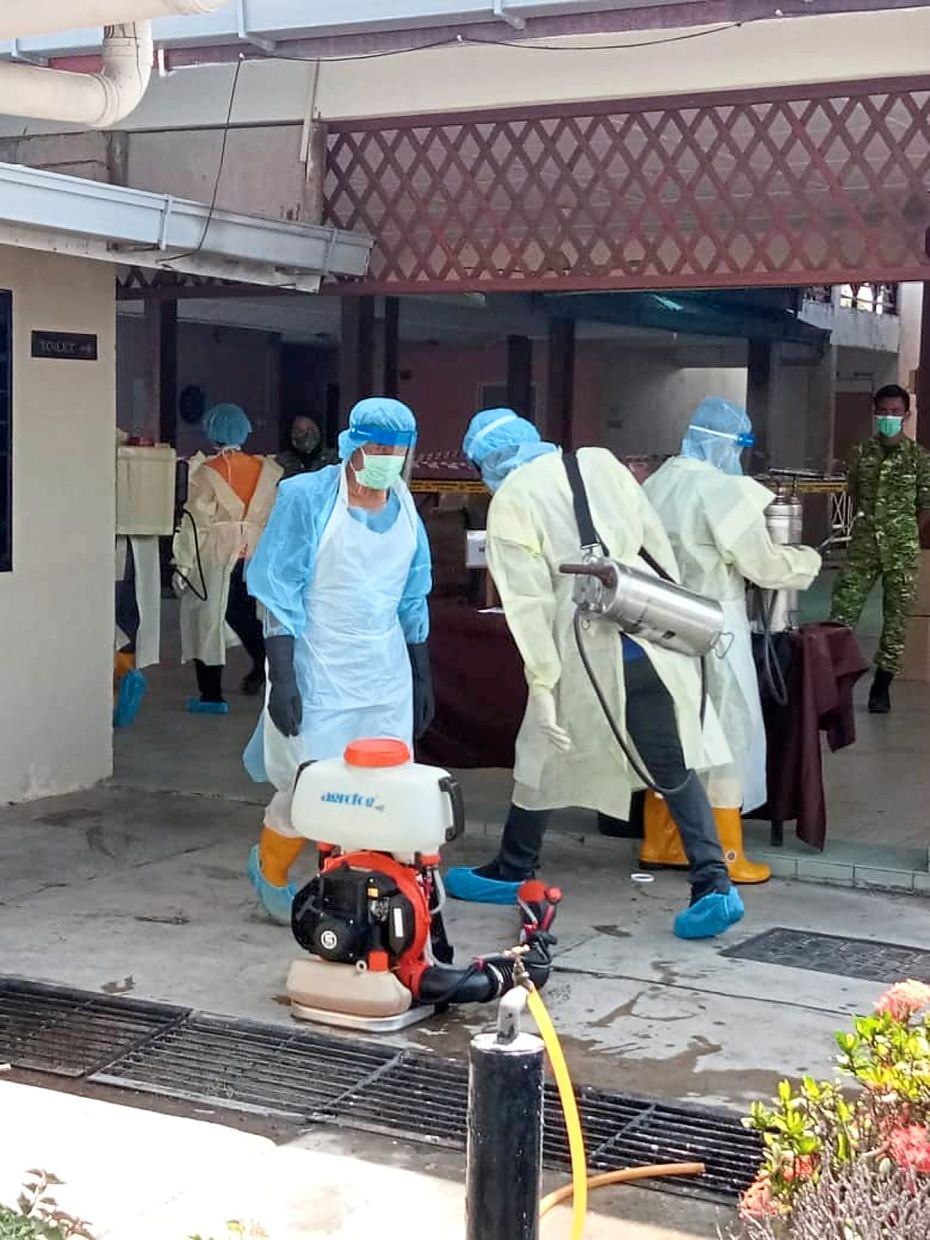 Health Ministry personnel disinfecting the public area of a budget hotel in Mersing, Johor.