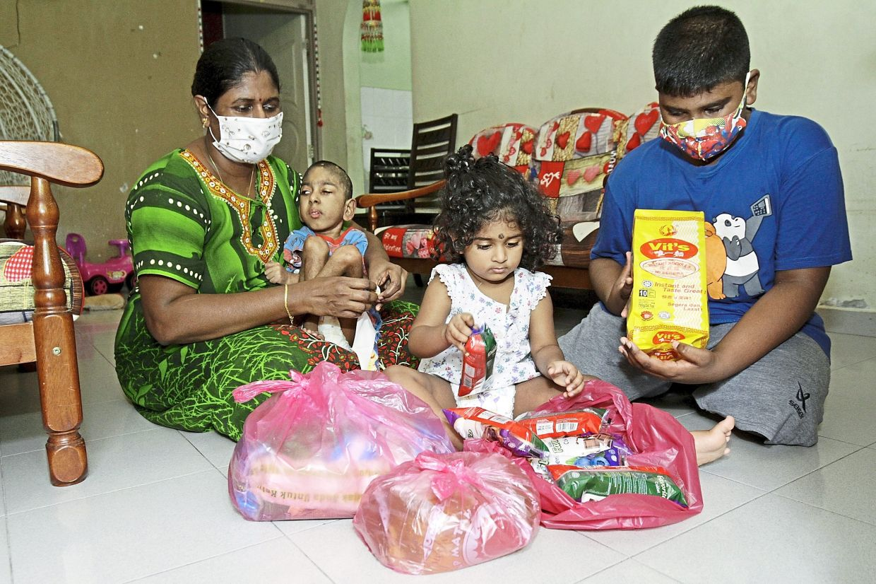 (From left) Vasanthi cradling her youngest child T. Hemendraa, seven, while her daughter Manggelleshwari, two, and son Yasshiilan, nine, look at the grocery items that they received at Sun Moon City flat in Paya Terubong, Penang.