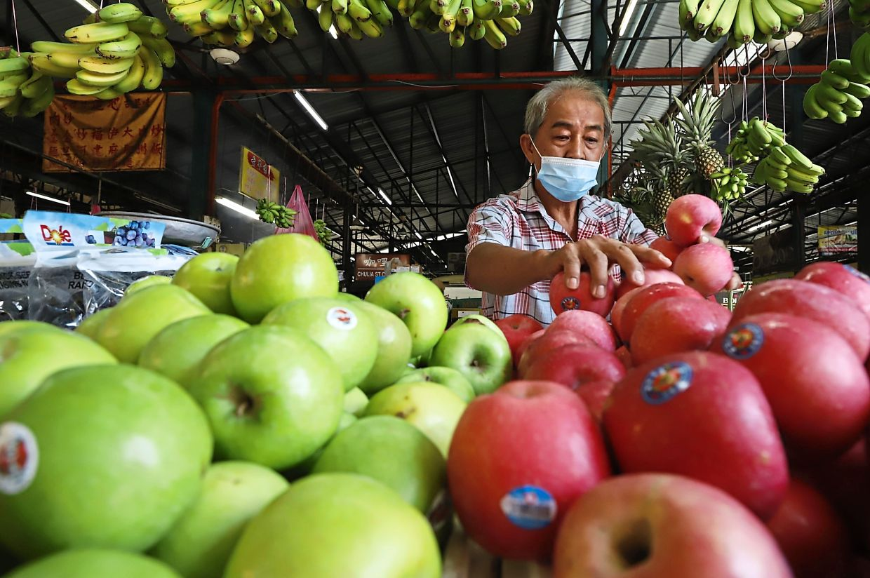 A trader arranging fruits at a stall.