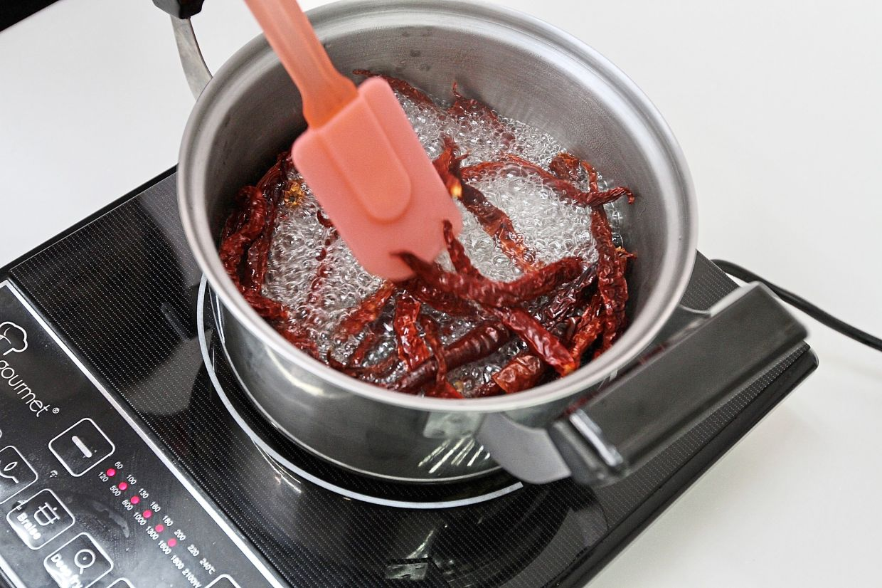 Boil the dried chillies in about half a cup of water before grinding them into a paste in the blender.