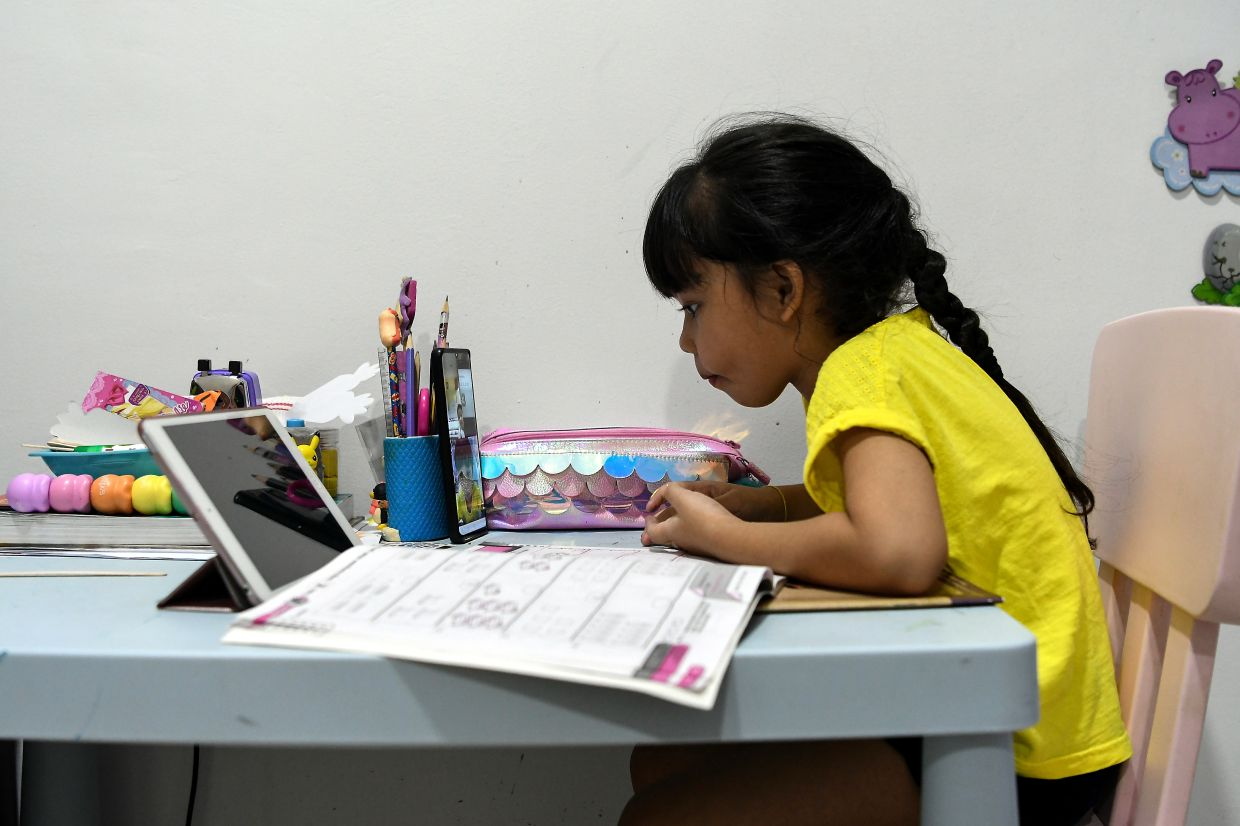 A young student following an e-learning session at home following the implementation of MCO. — Bernama
