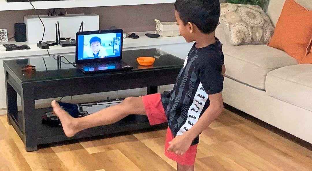 Roshan Sunil, Sageena's son, practising taekwondo as he follows the demonstration by his coach online.