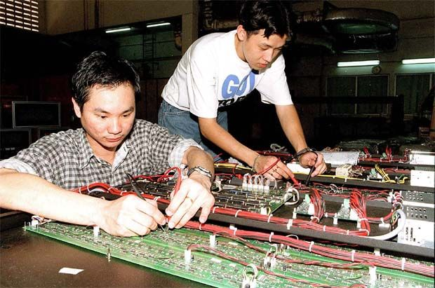 Technical staff at Industronics factory installing chips and other electronics gear on to the back of an electronic display system. - File pic