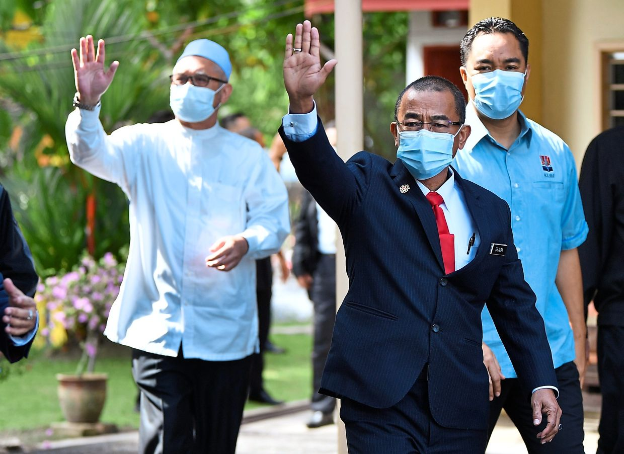 Court date: Dr Noor Azmi (centre) and Razman waving to members of the press as they arrive at the Magistrate's Court in Gerik, Perak.