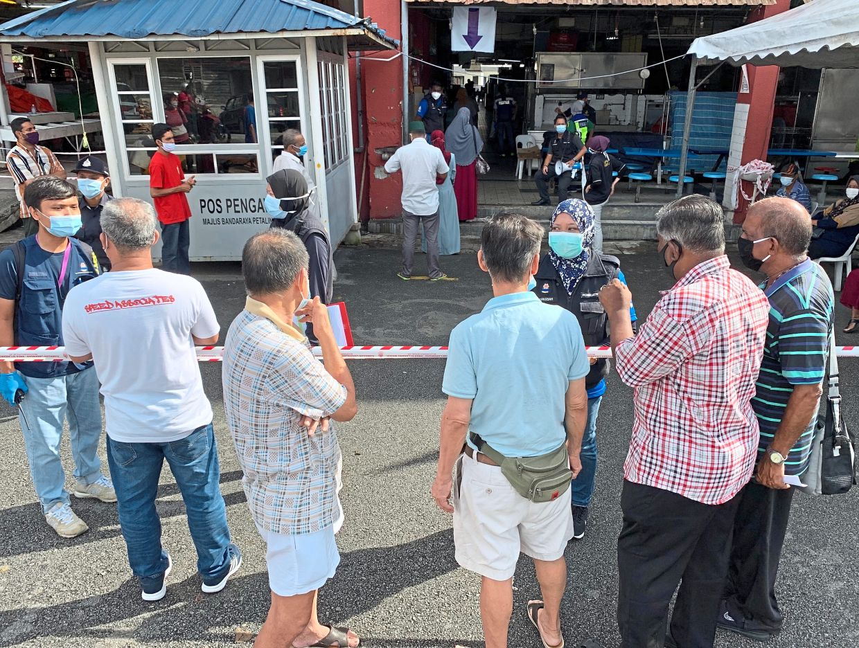 Excluded: Petaling District health officers listening to Jalan Othman market traders who are objecting to being left out of the group sent for Covid-19 test. — S.S.KANESAN/The Star