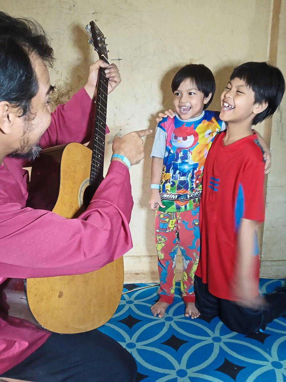 Azhar playing the guitar to keep his children, Aisya Umaira (right), 10, and Zara Zahirah, five, entertained while under lockdown.