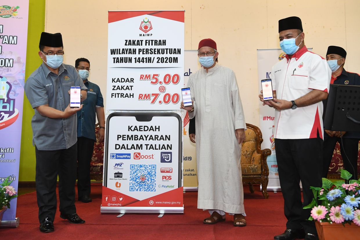 The launch of the MAIWP online zakat payment portal was attended by (from left) Federal Territory Islamic Affairs Department (Jawi) director Mohd Ajib Ismail, Zulkifli and MAIWP deputy CEO Mohd Nizam Yahya. — Bernama