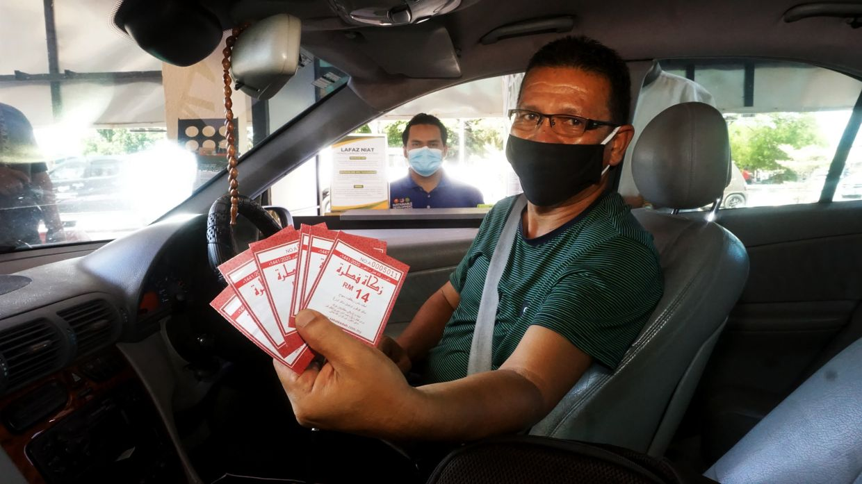 A member of the public showing the receipts for zakat payments made at the Kedah Zakat Board drive-through counter. — Bernama