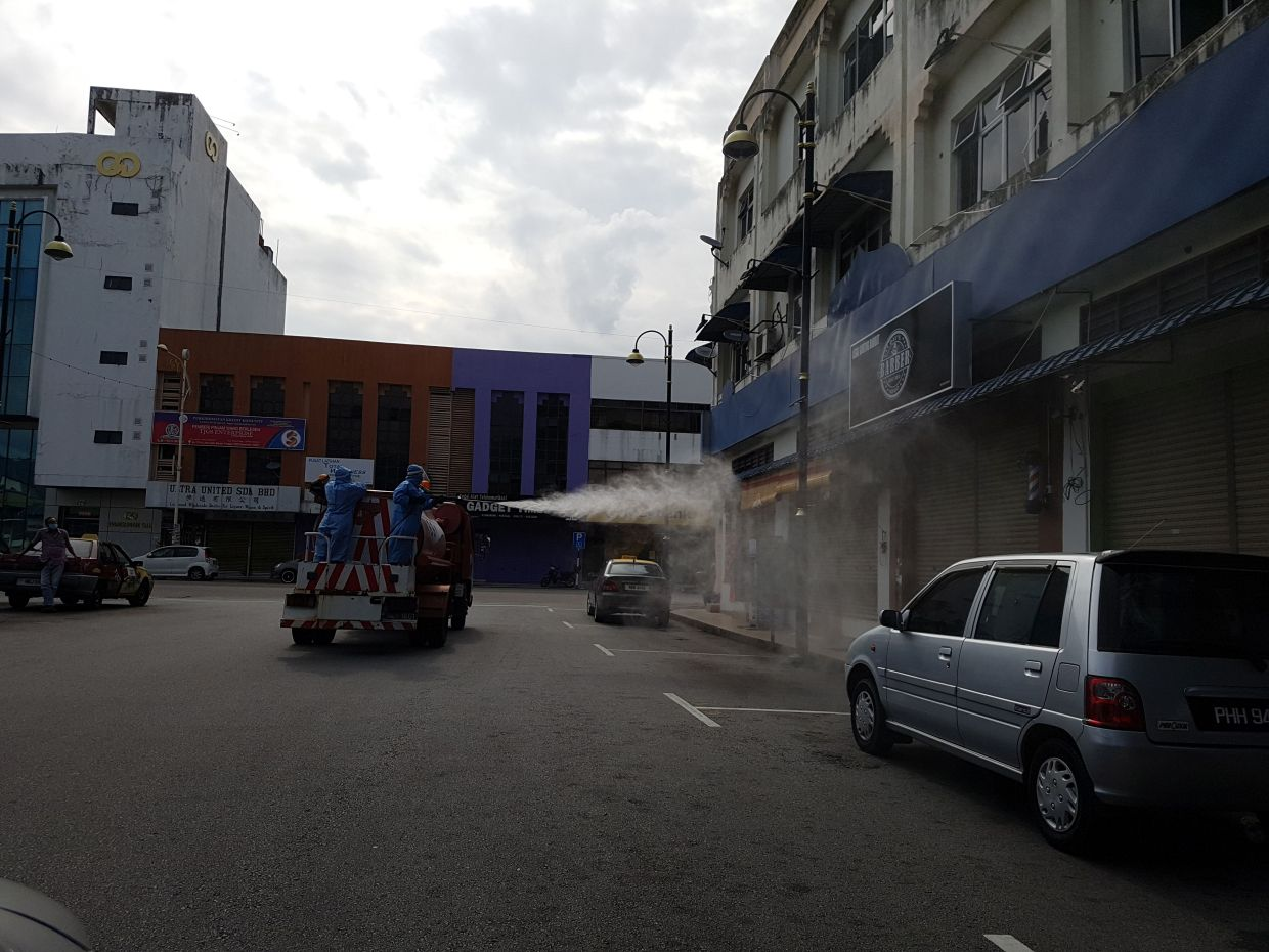 Seremban City Council workers carrying out cleaning and sanitising at business premises around the Seremban wet market.