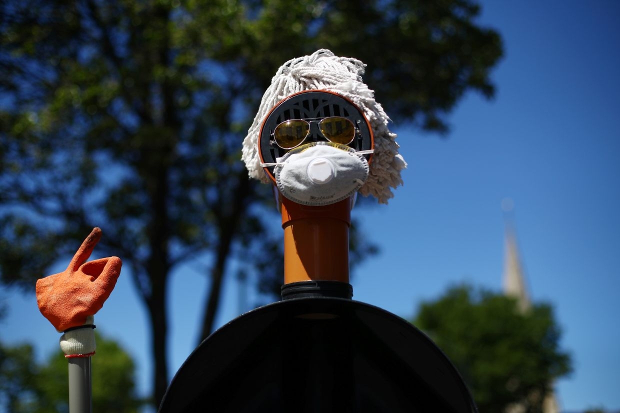 A sculpture surrounding a bollard consisting of plumbing materials, sunglasses and a protective face mask is seen in Lewisham following the outbreak of coronavirus disease in London. Photo: Reuters