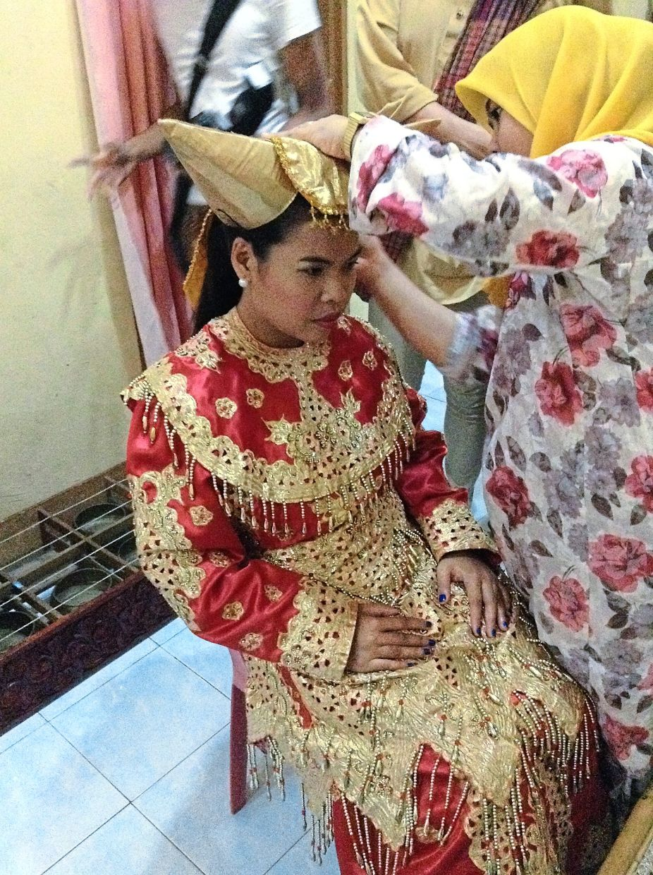 One of the villagers helps the 'bride' to don her traditional Adat Perpatih wedding gown.