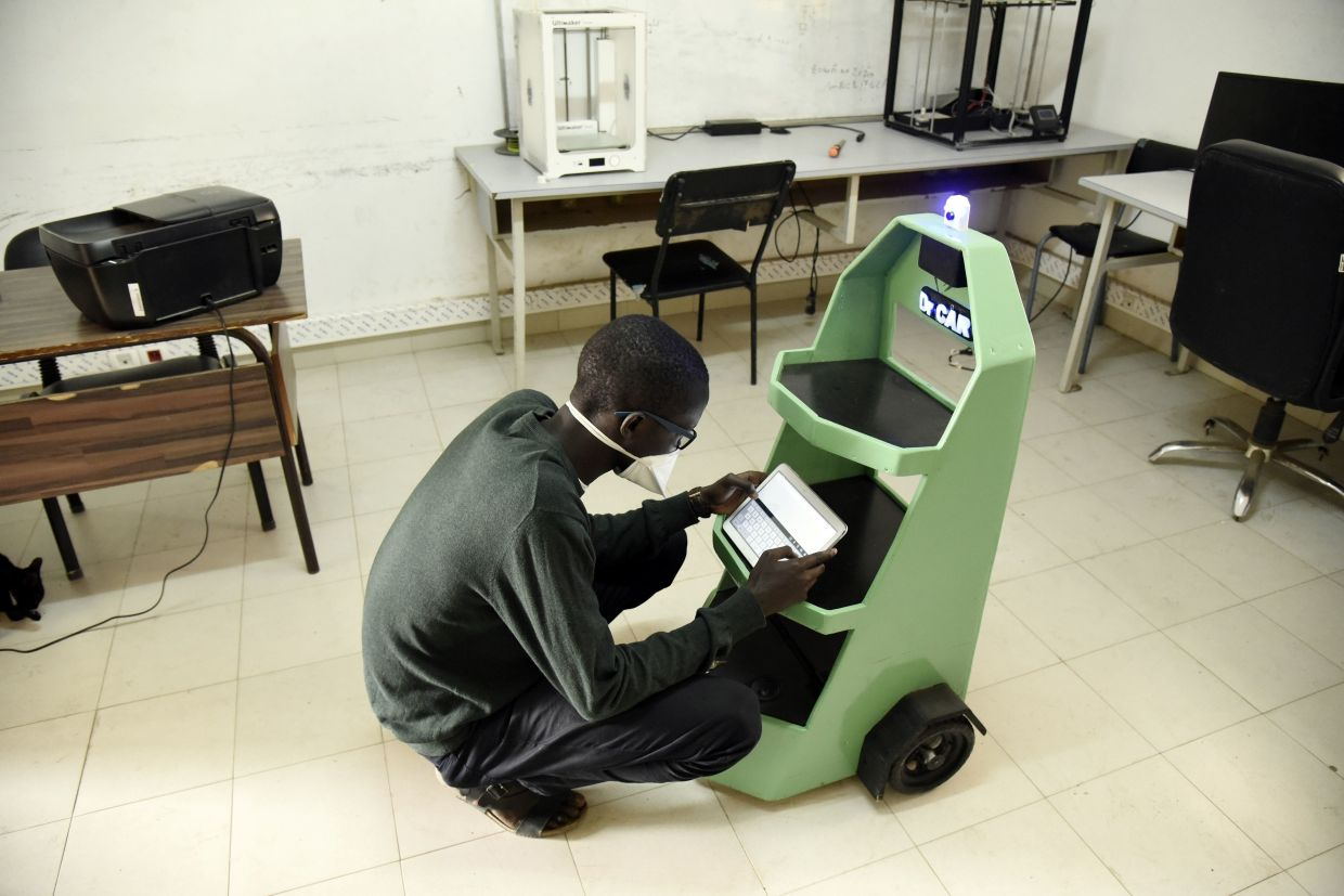 Kébé, a final year mechanical engineering student and coordinator of the 'Dr Car', handles a small robot in the school's lab.