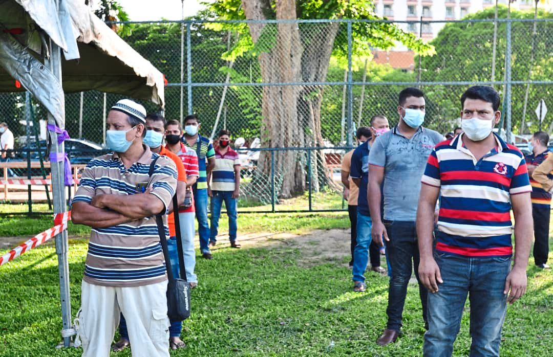 Foreign workers queue for their turn to be screened for the Covid-19 virus at Padang Polo in Penang.