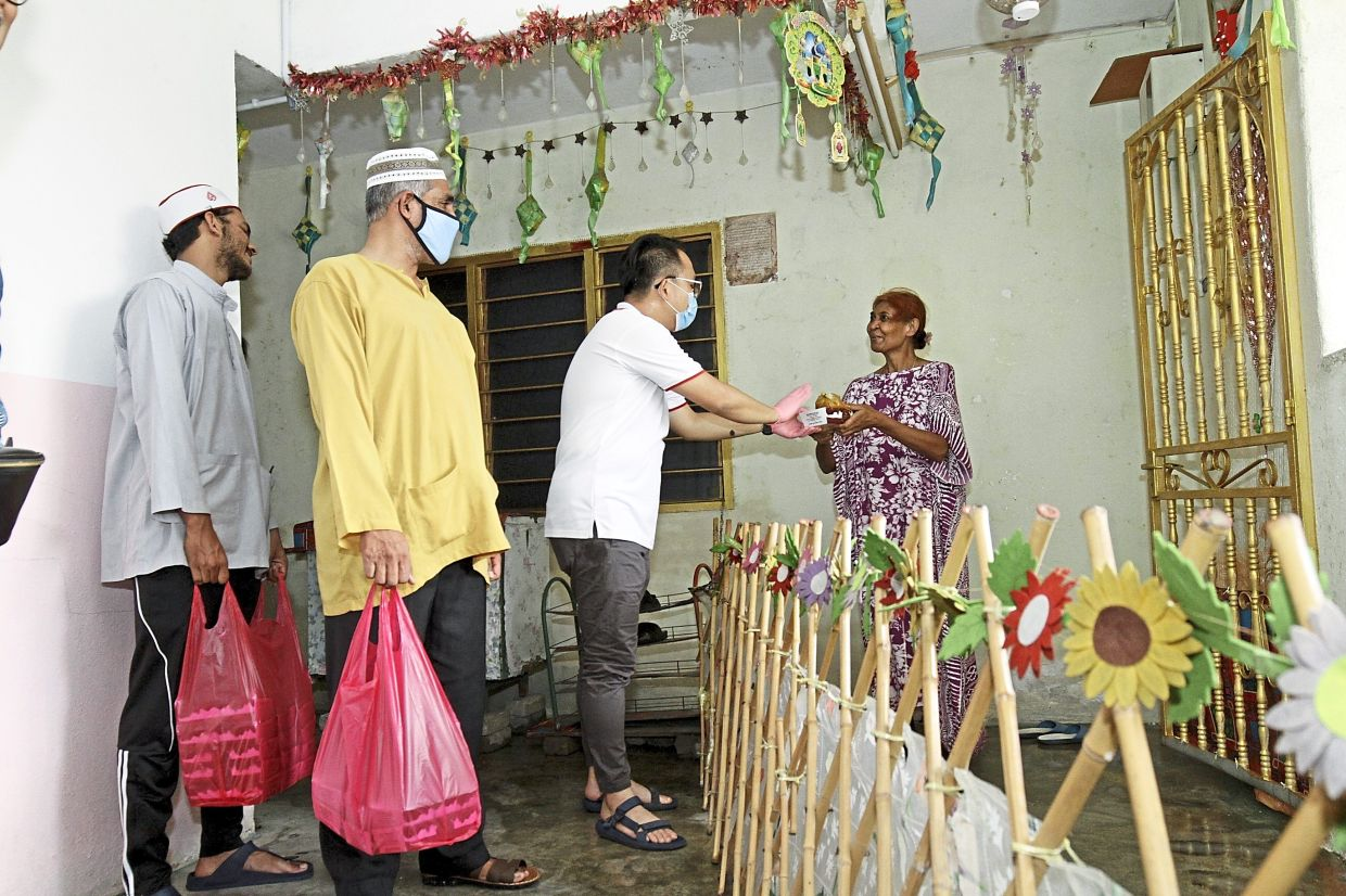 Gooi handing over packed rice and dates to Nazira at her door. — Photos: CHAN BOON KAI/The Star