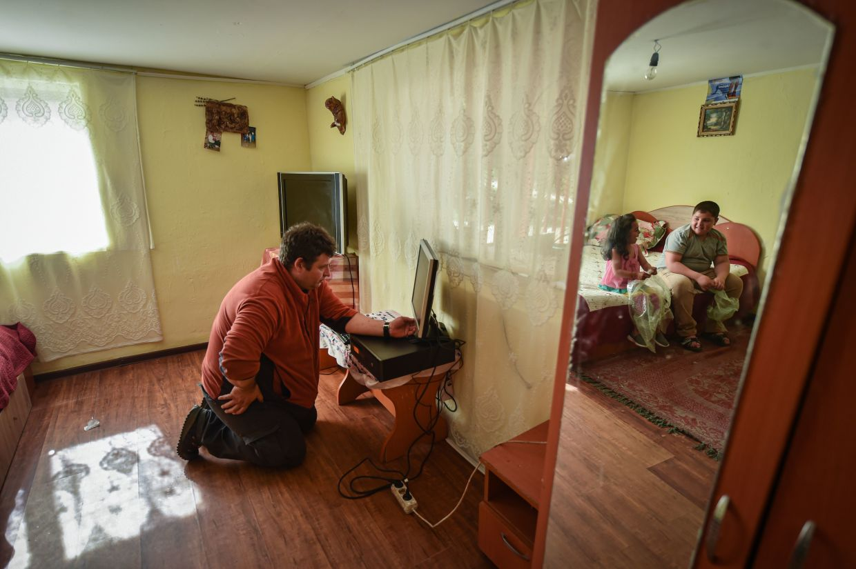 Lucian Cojocaru, a volunteer from 'Casa Buna' (The Good Home) NGO, installs a desktop computer to be used for remote schooling in Nucsoara village. Donated by several NGOs, the computers are meant to provide schoolchildren staying at home access to remote classes amid the novel coronavirus Covid-19 pandemic. — AFP