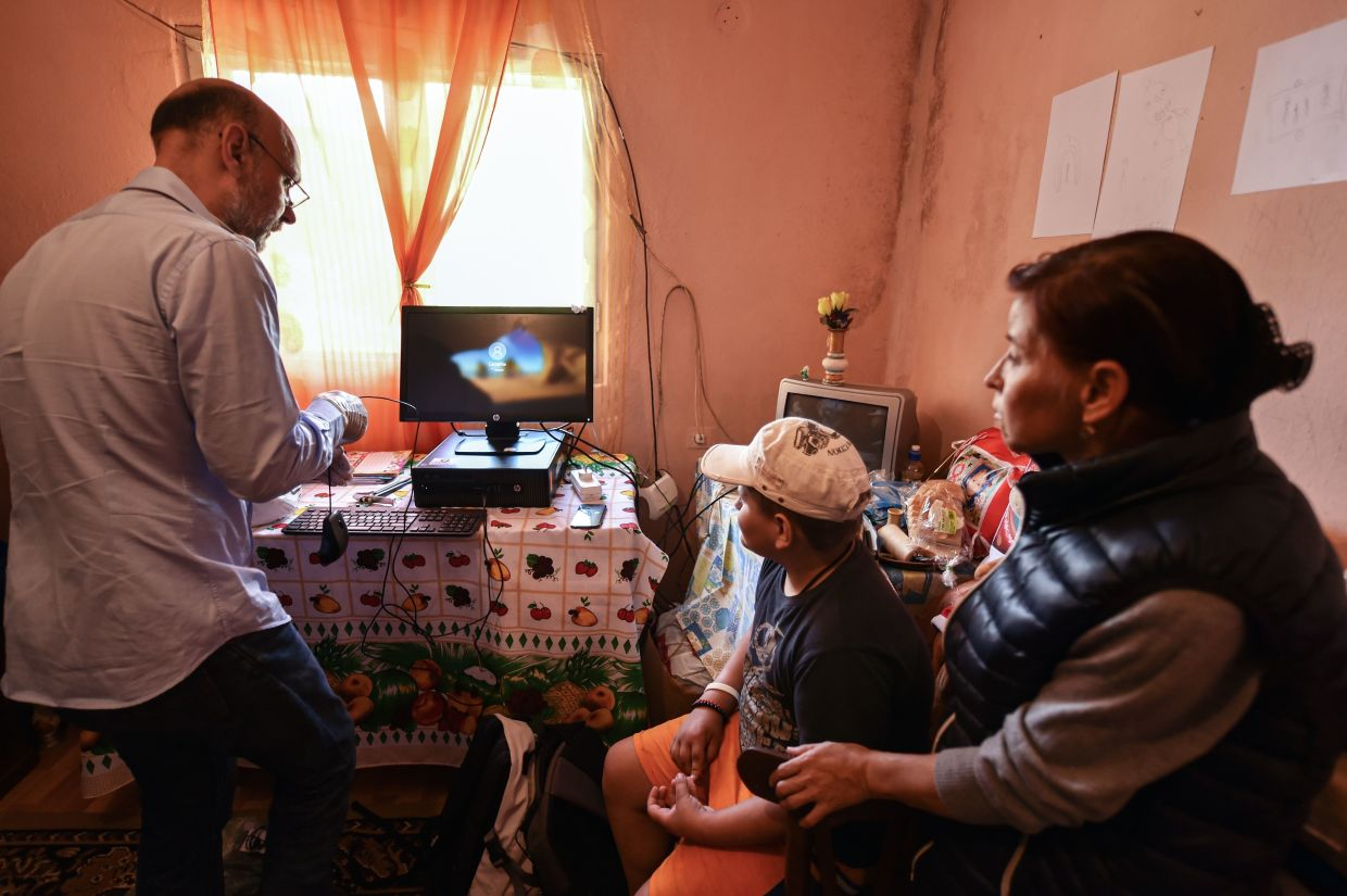 One of the volunteeers from 'Casa Buna' (The Good Home) NGO (left) instructs a child and his mother on how to use the newly installed desktop computer in Nucsoara village. — AFP