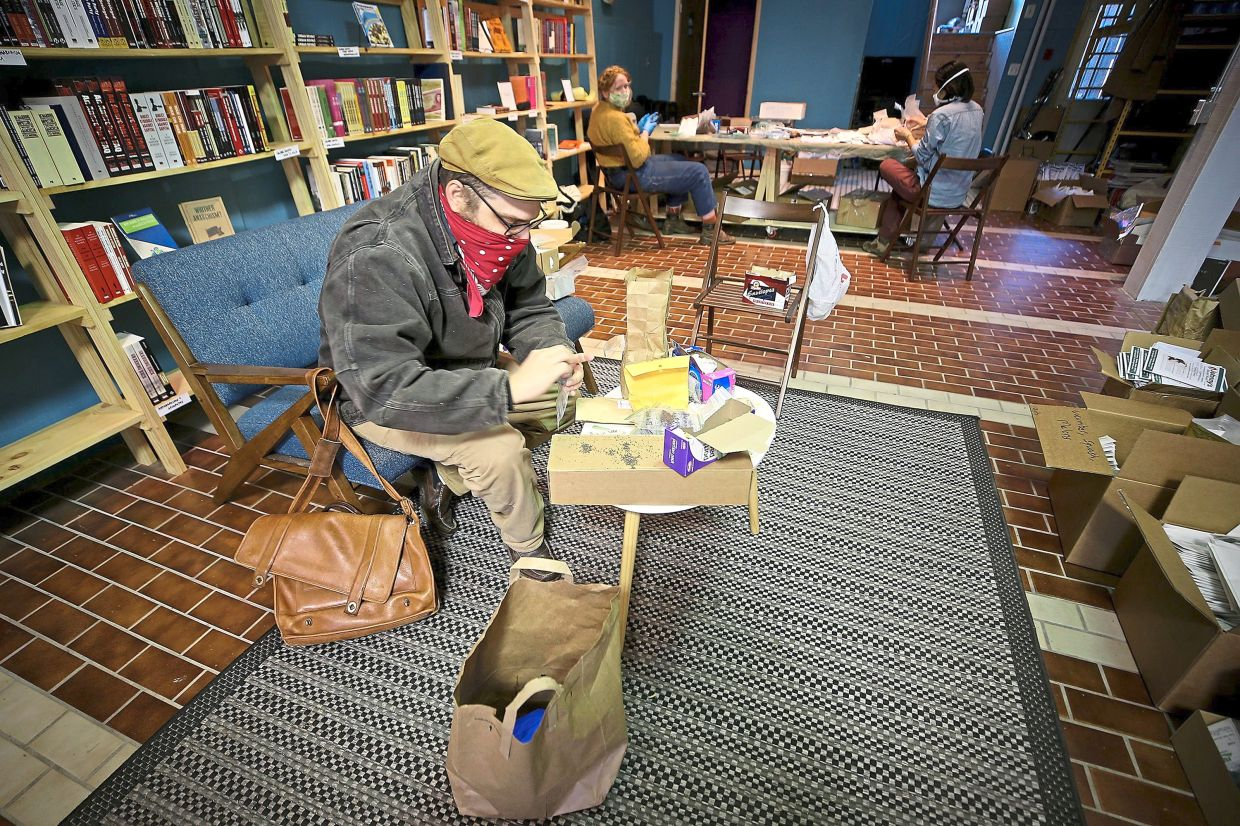 Kleinman (foreground), Illes (background, left)and Kim packing seeds inside the Making Worlds bookstore in Philadelphia, on April 22. A huge amount of seeds are shipped to gardeners around the United States.