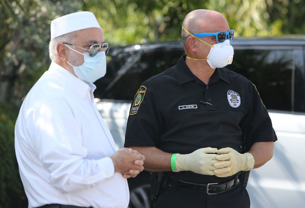 Imam Dr Abdul Hamid Samra talks with Miami Gardens, Florida, police officer Carlos Austin, as they watch dozens of cars drive through the parking lot of the Islamic Center of Greater Miami to collect food on April 21.