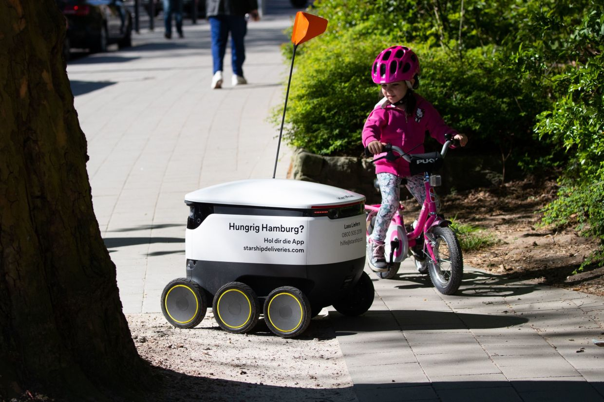 A delivery robot with food drives through the streets of Hamburg on its way from an organic food shop to a customer. The Starship delivery robot, which has sensors, cameras, GPS and radar, brings food from shops and restaurateurs to customers.