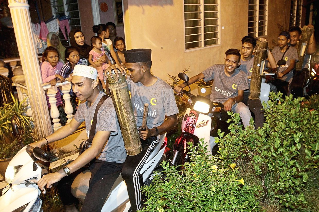 Residents looking at the Geng Gerak Sahur Teluk Bahang youths providing friendly sahur calls for residents to wake up for their pre-dawn meal during the fasting month last year. Photos: Filepic