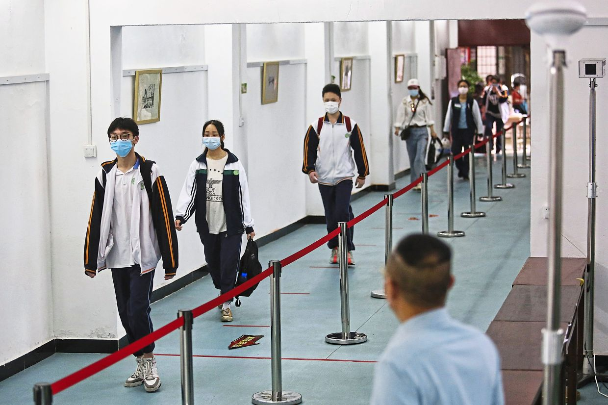 Keep a distance: Malaysian school students will have to maintain strict social distancing protocols just like their counterparts in China to help curb the spread of Covid-19 once schools reopen here. – AP