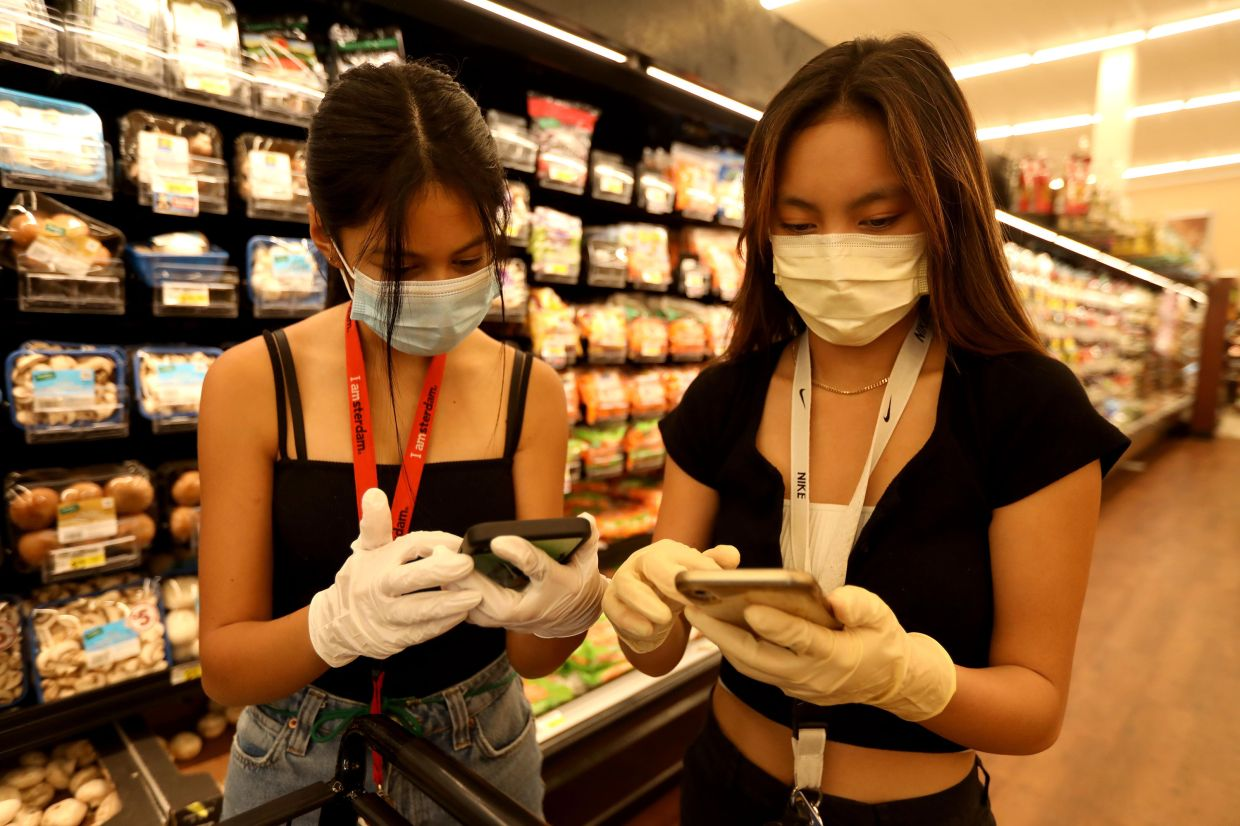 Riel, 16, left, and Mendoza, 17, fill an online order at Albertson's grocery store in Valencia, California. Both are volunteers with Six Feet Supplies, a free service started by local teenagers to help the most vulnerable during the coronavirus outbreak.