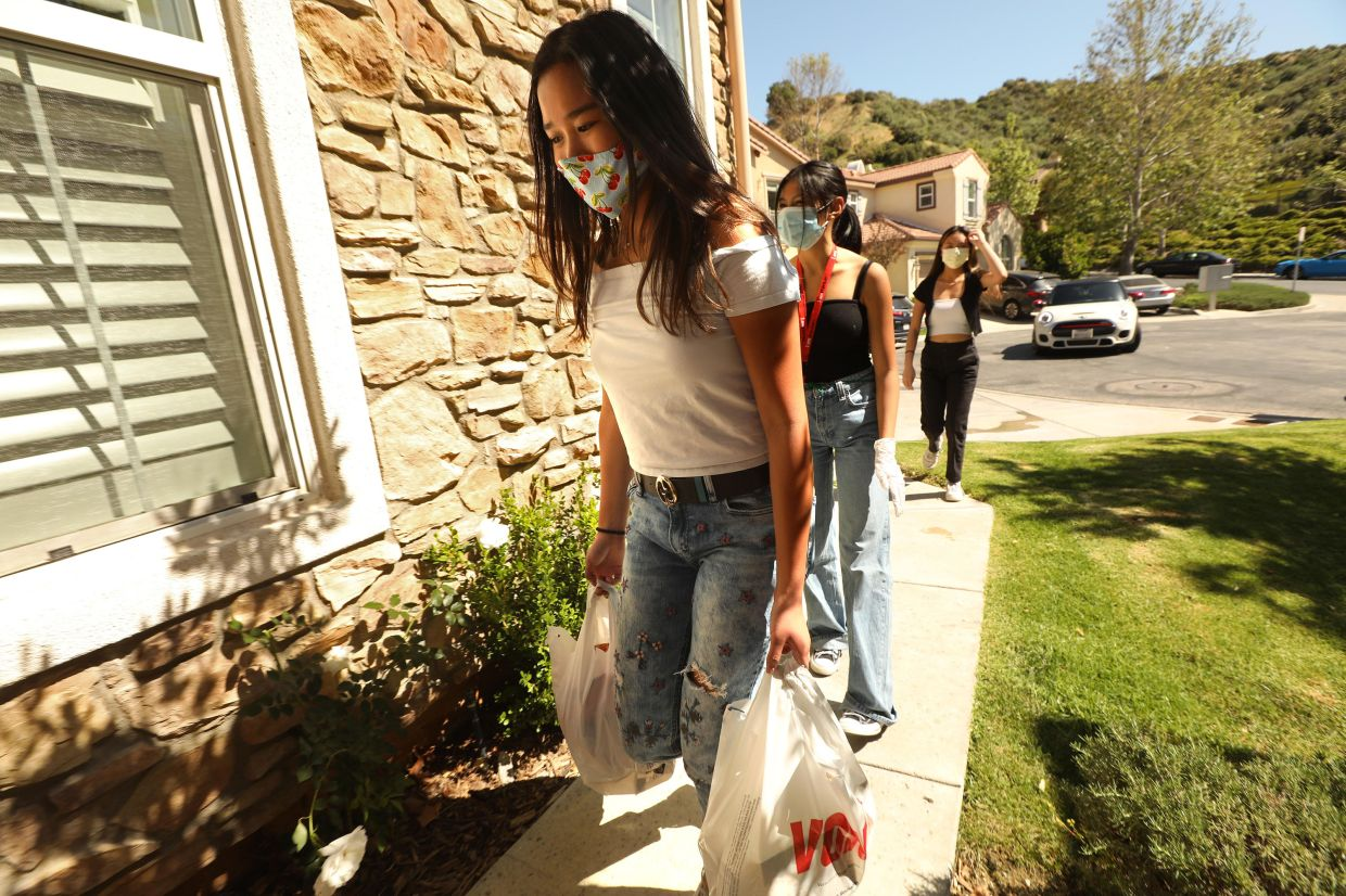 From left, Busnawi, 16, Riel, 16, and Mendoza, 17, deliver an online grocery order in Santa Clarita, California, as the teens volunteer with Six Feet Supplies, shopping for housebound people amid the coronavirus pandemic.