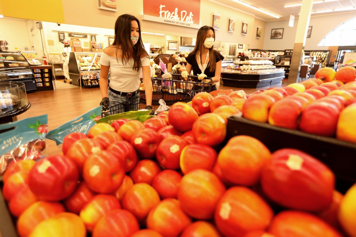 Busnawi, 16, left, and Mendoza, 17, shop for groceries at an Albertsons store in Valencia, California, while volunteering for the Six Feet Supplies service.