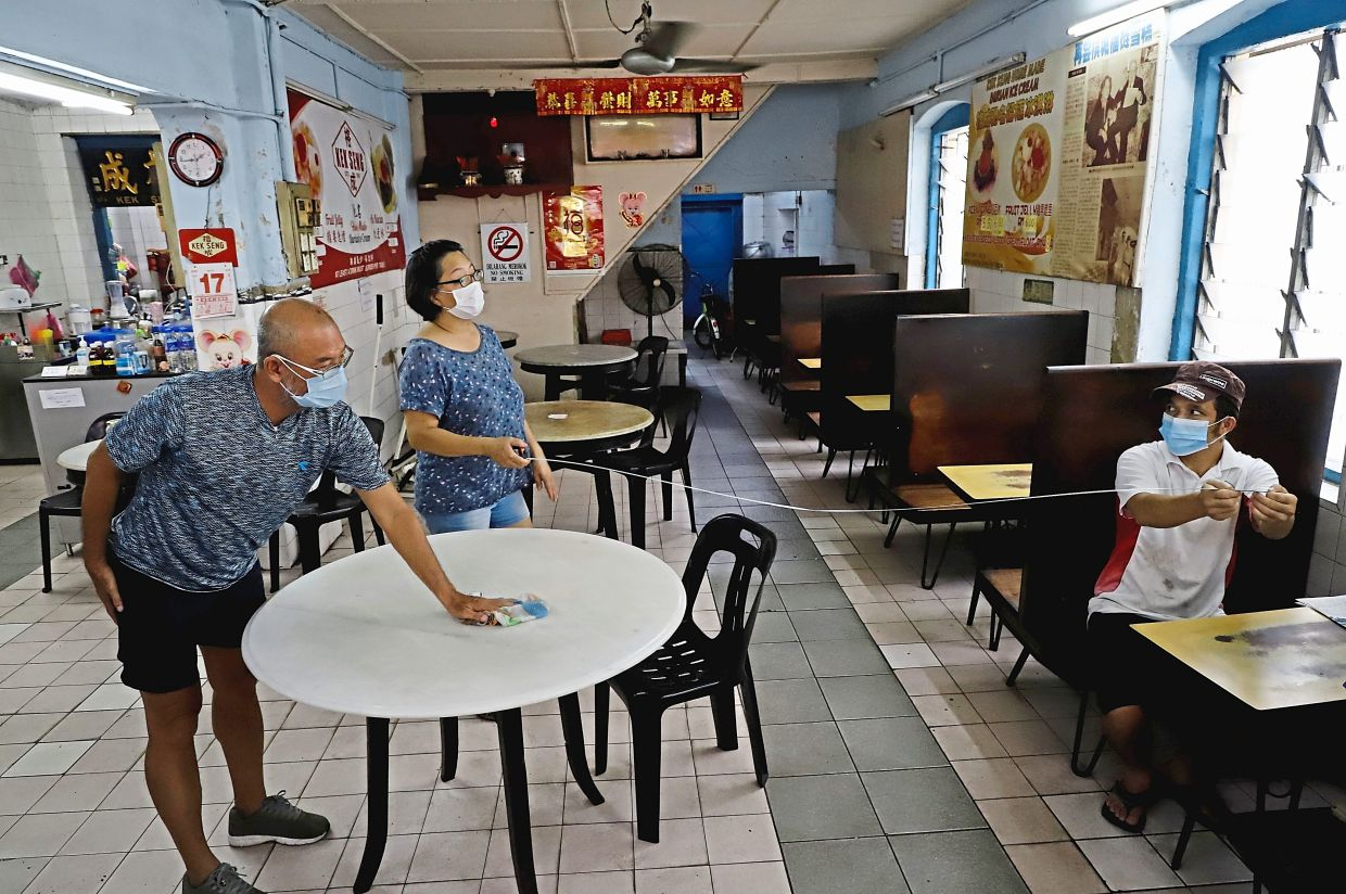 Kek Seng coffee shop owner Chiow Sow Lei (middle), 53, and her workers preparing to serve customers at the shop in Penang Road.