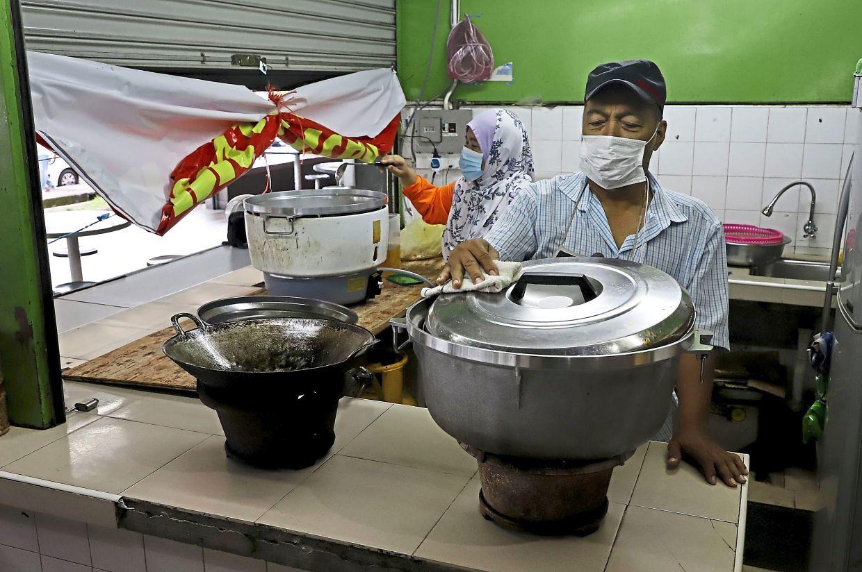 Afandi Puteh, 57, and his wife Karsinah Ranopaviro, 54, operating their stall in Bayan Baru.