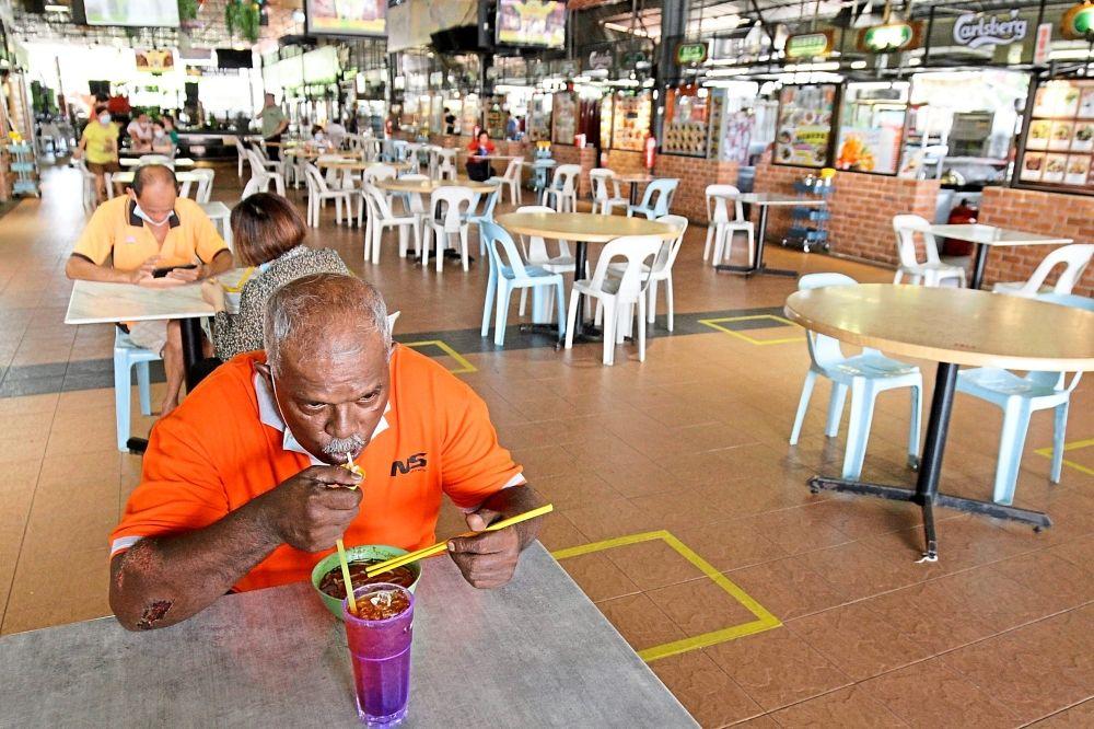 S. Govindasamy, 56, enjoying a bowl of laksa at a food court in Weld Quay, Penang.