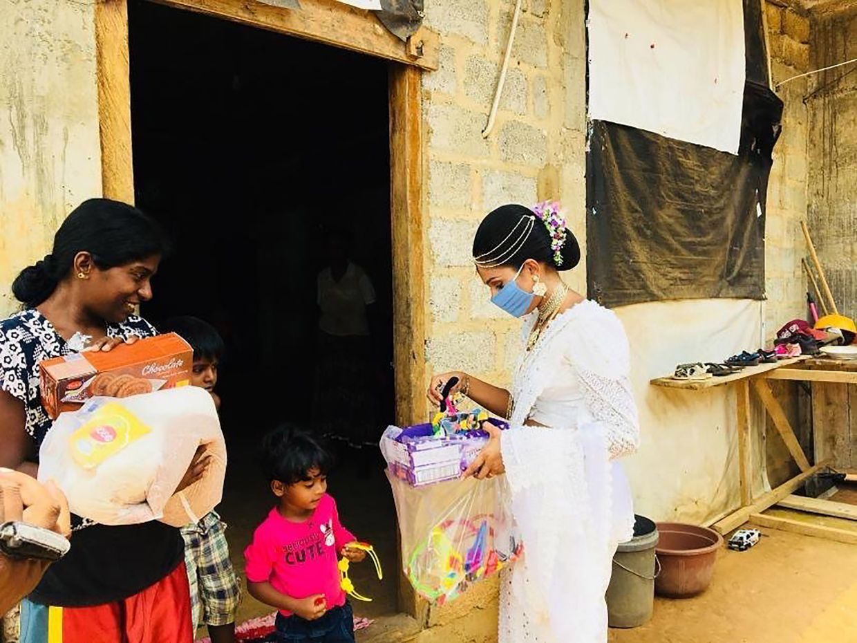 In her white lace sari and a jeweled wedding headpiece, Pawani distributed food to some of those who needed aid the most.