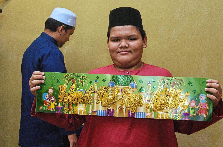 Mohamad Danial's task is to put up Hari Raya decorations.