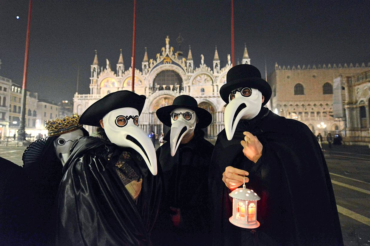 Participants in the 'Plague Doctors Procession' at Saint Mark Square in Venice on Feb 25, wear replicas of the beaked face masks doctors wore in the Middle Ages to avoid contracting the bubonic plague. — AFP