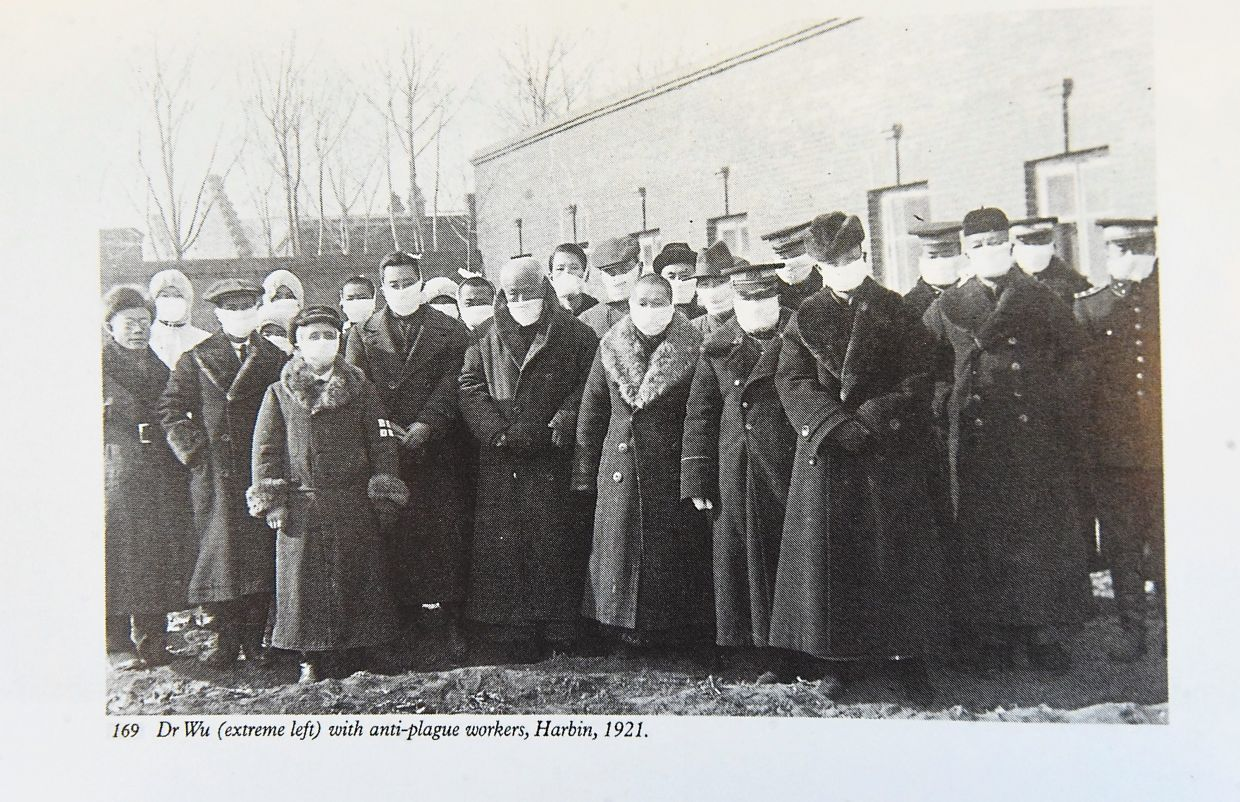 A photo from Dr Wu's book showing the doctor (left) with plague workers in Harbin, China, in 1921, all wearing face masks.