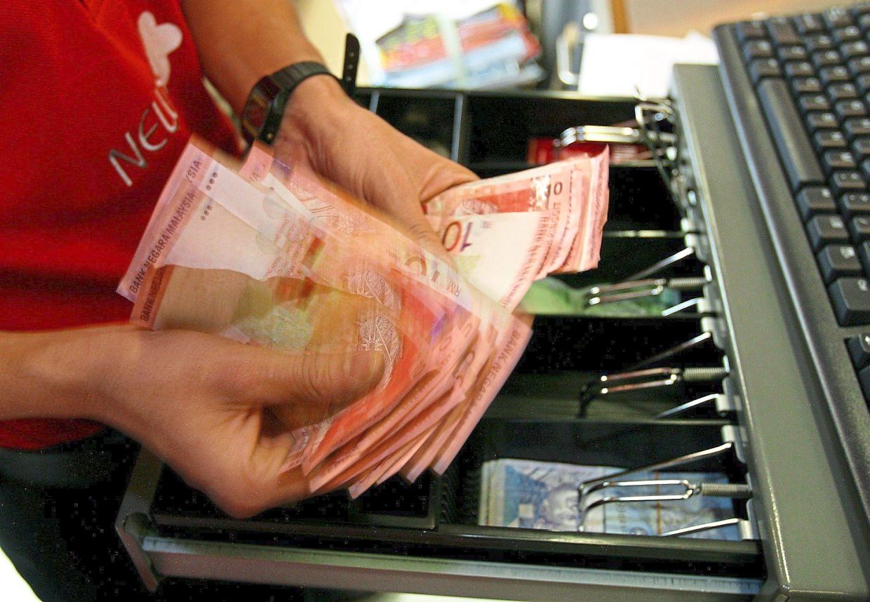A shop assistant counts cash in the register at a supermarket in this filepic. We should wash our hands with soap and water after handling money as it may be contaminated with the SARS-CoV-2 virus.