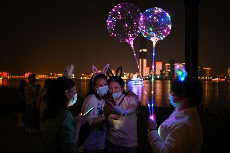 It's Friday night out again as women wearing face masks take a selfie picture in Hankou Park in Wuhan, in China's central Hubei province on Friday (May 22). - AFP